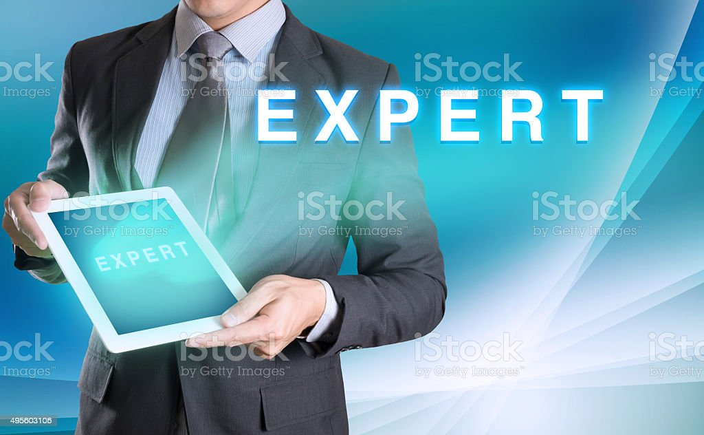 businessman holding tablet with EXPERT word with abstract backgr stock photo