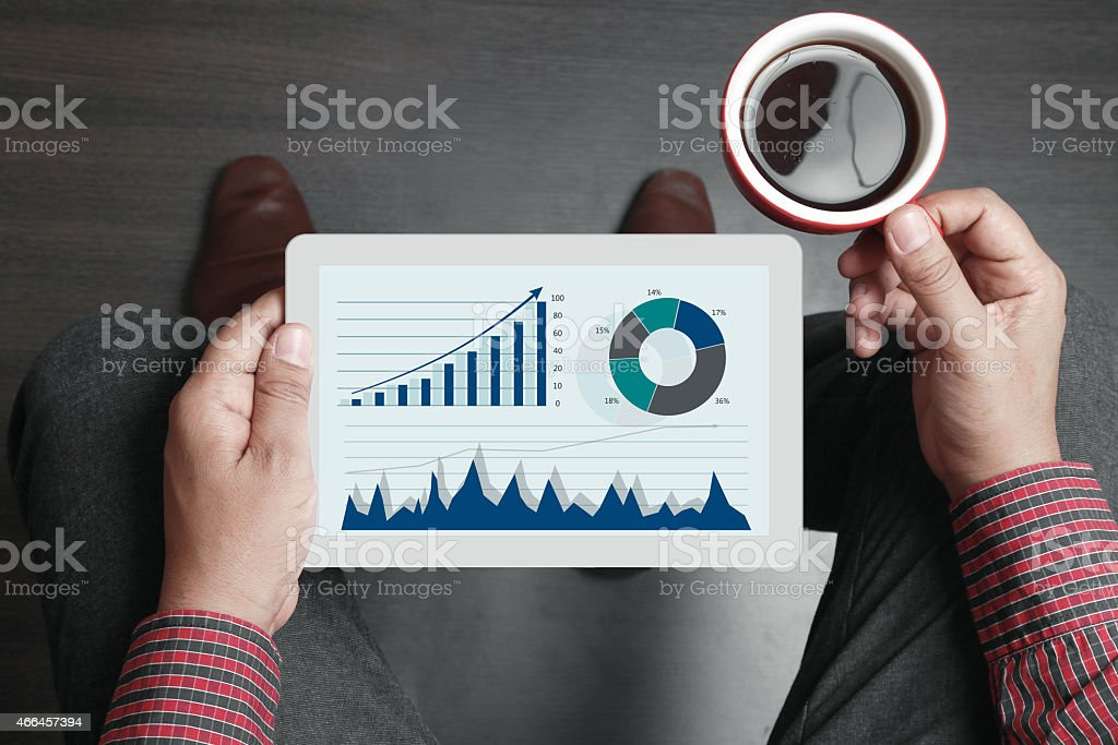 Businessman holding tea cup and digital tablet stock photo