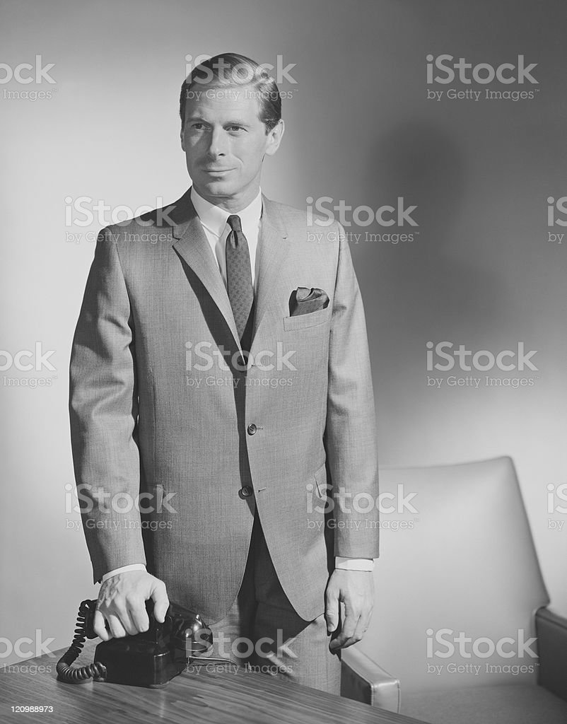 Businessman holding telephone receiver stock photo