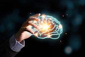 istock Businessman holding the blue virtual brain. Creative new business idea concept. 1226588125
