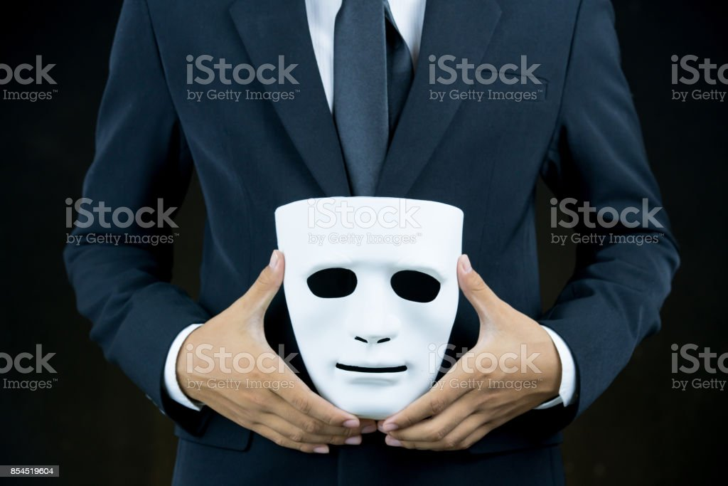 businessman holding the white mask in the hand on black background. stock photo