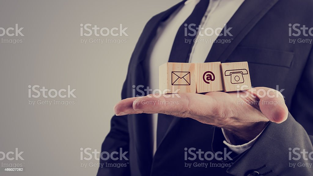 Businessman holding three wooden cubes with contact symbols stock photo