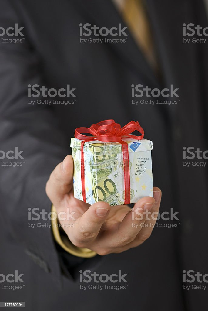 Businessman holding tiny gift box made of banknotes stock photo