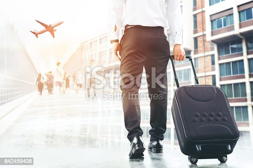 istock Businessman holding trolley bag going up on travel 842459408