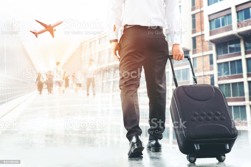 Businessman holding trolley bag going up on travel stock photo