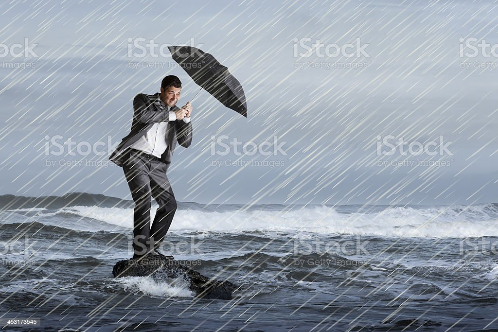 Businessman holding umbrella on rock in rough surf and rain stock photo