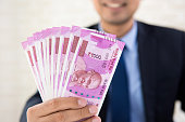 istock Businessman holding up Indian rupee banknote money 946711054