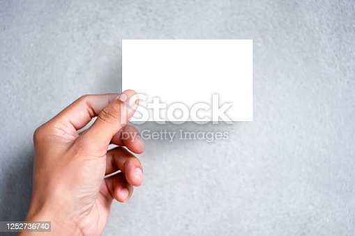 Hand holding blank plain white business card design mock up. Clear call id card mock up template hold arm. Visit pasteboard paper surface display front. Small pure offset name card print.Logo branding