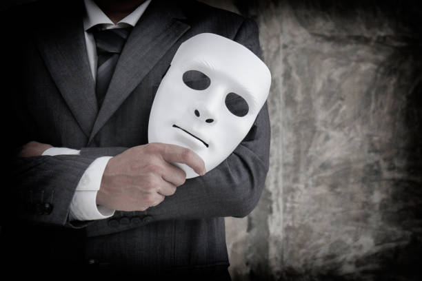 Businessman holding white mask in his hand dishonest cheating agreement.Faking and betray business partnership concept stock photo