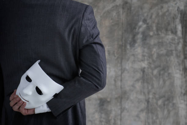그의 손에 흰색 마스크를 들고 사업가 부정직 부정 행위 계약. 비즈니스 파트너십 개념의 위조 및 배신 - 악한 뉴스 사진 이미지