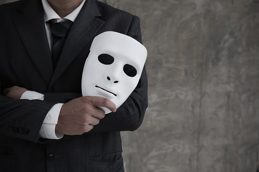 istock Businessman holding white mask in his hand dishonest cheating agreement.Faking and betray business partnership concept 1172304383