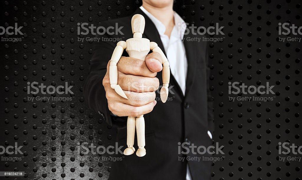 Businessman holding wooden figure, on black aluminum texture background stock photo