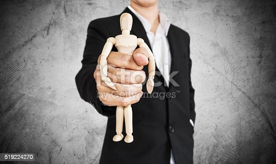 istock Businessman holding wooden figure, on concrete texture background 519224270