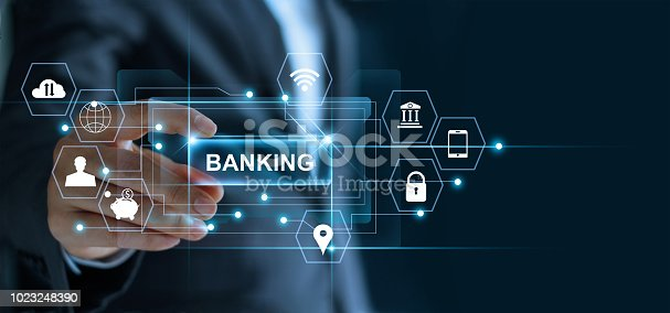 istock Businessman holding word banking in hand with icon network connection on virtual screen dark background 1023248390
