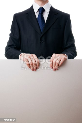 istock Businessman holds a blank sheet of cardboard 179963624