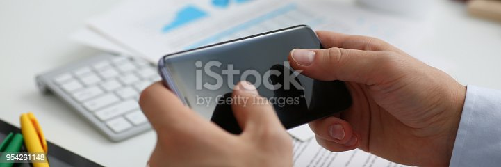 936543982istockphoto A businessman holds a new smartphone in his hand 954261148