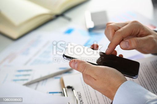 936543982 istock photo A businessman holds a new smartphone 1060558500