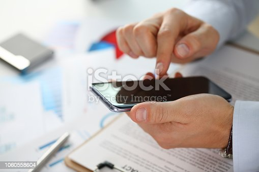 936543982 istock photo A businessman holds a new smartphone 1060558604