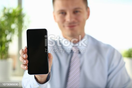 936543982 istock photo A businessman holds a new smartphone 1073095530