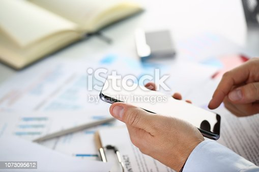 936543982 istock photo A businessman holds a new smartphone 1073095612