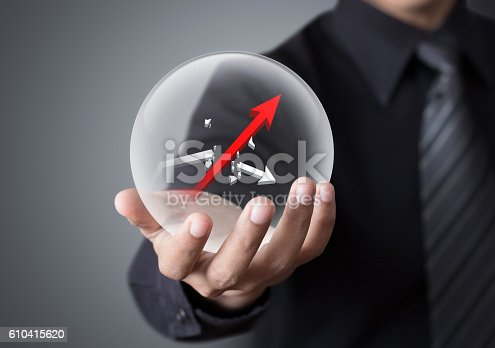 istock Businessman holds crystal ball with rising red graph 610415620