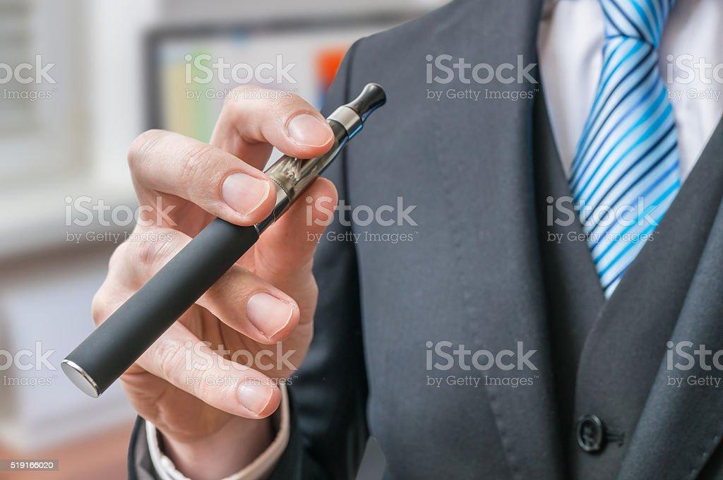 Technology Management Image: Businessman Holds Exigarette Or Vaporizer In Hand Stock