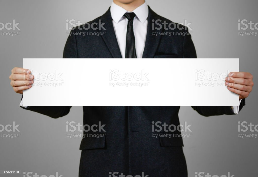Businessman holds in hands a long, narrow paper. Empty for your text. Isolated on gray background stock photo