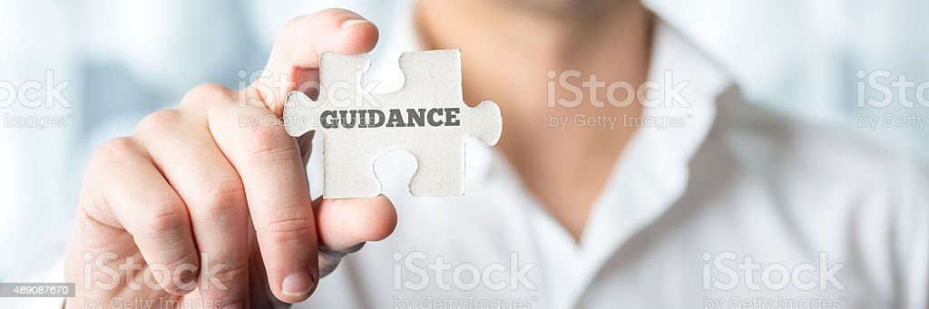 Businessman Holds Puzzle Piece with Guidance Text stock photo