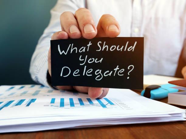 Businessman holds sign What Should You Delegate. Delegation concept. stock photo