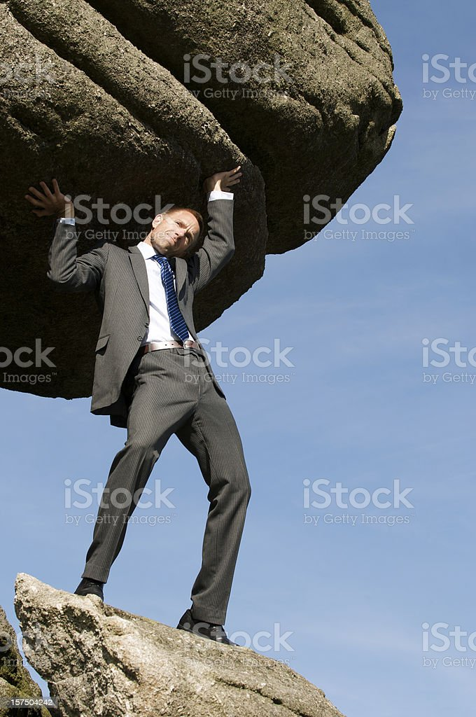 Businessman Holds Up Huge Boulder in the Sky stock photo