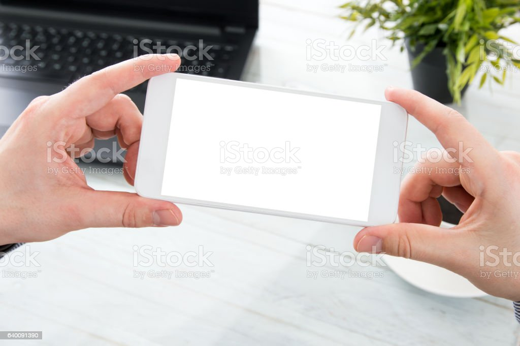 Businessman holds white smartphone with empty screen stock photo