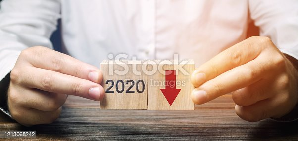 istock Businessman holds wooden blocks 2020 with down arrow. Economic crisis and recession. Bankruptcy and finance crisis. Analysis and analytics. Results of the year 1213068242