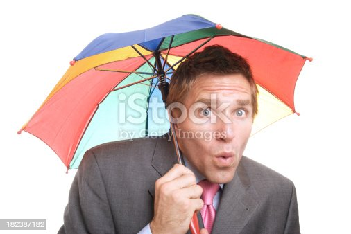 Businessman huddles under an undersized colorful umbrella against white background
