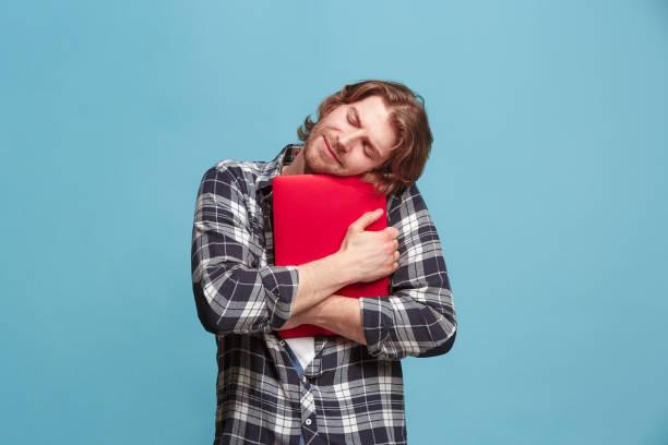 Homme d'affaires étreignant ordinateur portable sur bleu - Photo