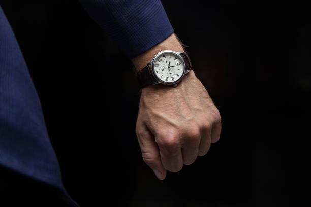 ビジネスマンは会議に急ぐ - 時間外労働腕時計 ストックフォトと画像