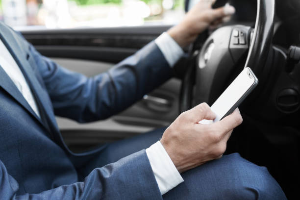 Businessman ignoring safety, texting on smartphone and driving car stock photo