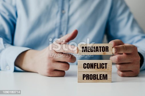 Businessman in a blue shirt arranges wooden jigsaw blocks with the word CONFLICT, MEDIATOR. Problem solving concept using a mediator, help during conflicts.