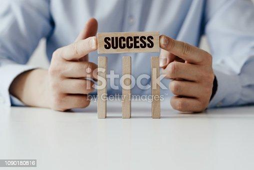 958939552istockphoto Businessman in a blue shirt arranges wooden jigsaw blocks 1090180816
