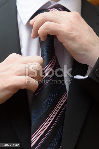istock Businessman in a business suit straightens his tie. 945770242
