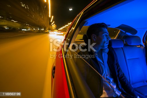 Modern businessman driving on a car back seat at night. About 25 years old, Caucasian male.