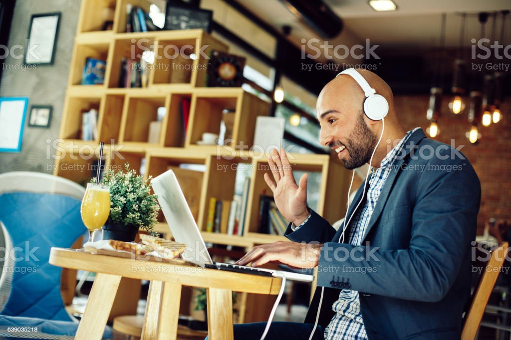 Businessman in a cafe at breakfast making video call stock photo