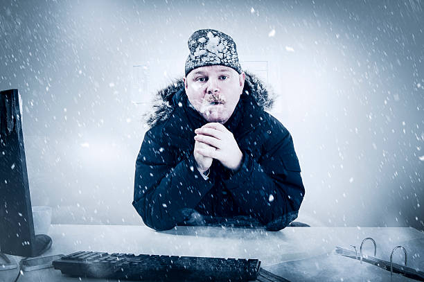 Businessman in a Cold Office with Snow and Ice stock photo