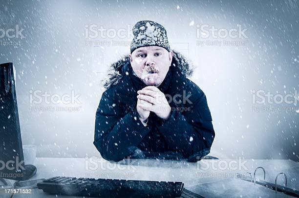 Businessman In A Cold Office With Snow And Ice Stock Photo - Download Image Now