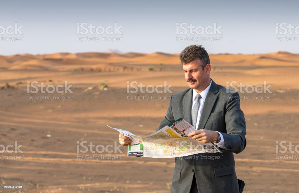 businessman in  a desert with a suitcase, looking at a map royalty-free stock photo