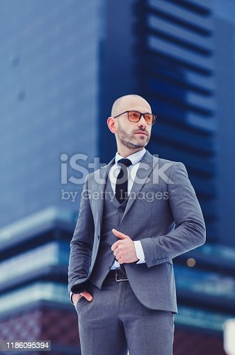 businessman in a gray suit is standing near a skyscraper or business center
