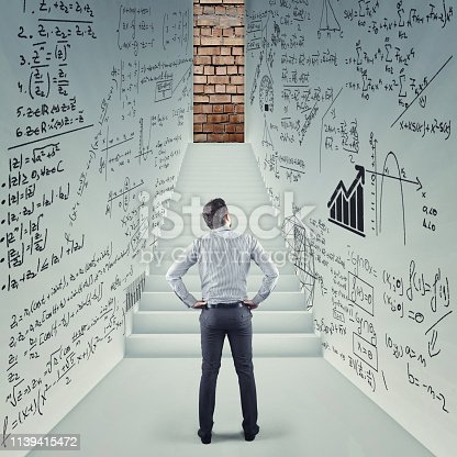Businessman in a hall trying to solve math problem drawn on walls. Stairs leading to a blocked door.