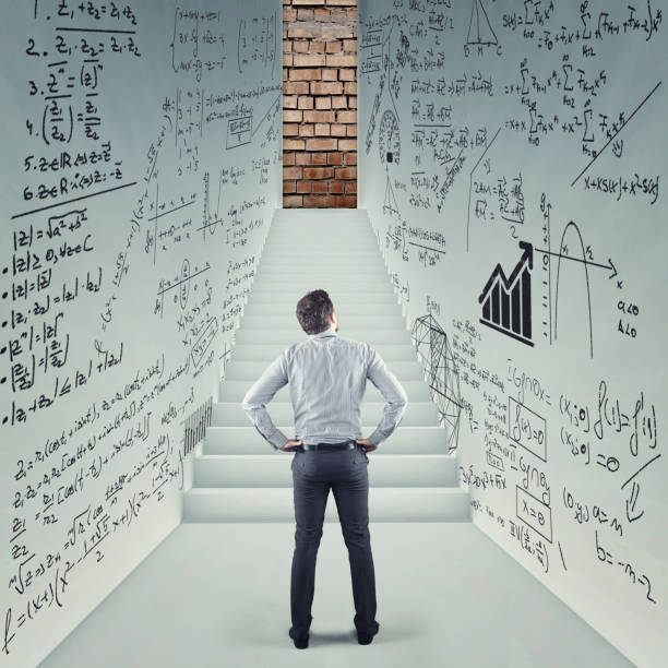 businessman in a hall trying to solve math problem drawn on walls. stairs leading to a blocked door. - formula 1 стоковые фото и изображения