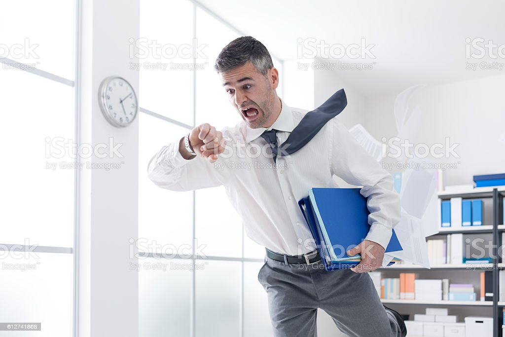 Businessman in a hurry checking time stock photo