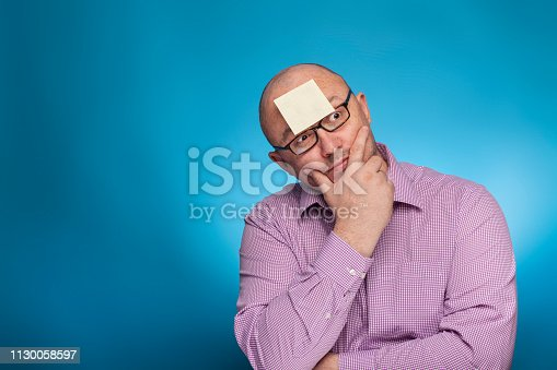 istock A businessman in a piked shirt has a blank post it on the forehead,  on the blue background. 1130058597
