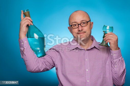 istock A businessman in a piked shirt has a bottle and a glass of wine in his hand,  on the blue background. 1130058647